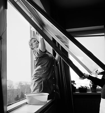 Nainen pesee ikkunaa